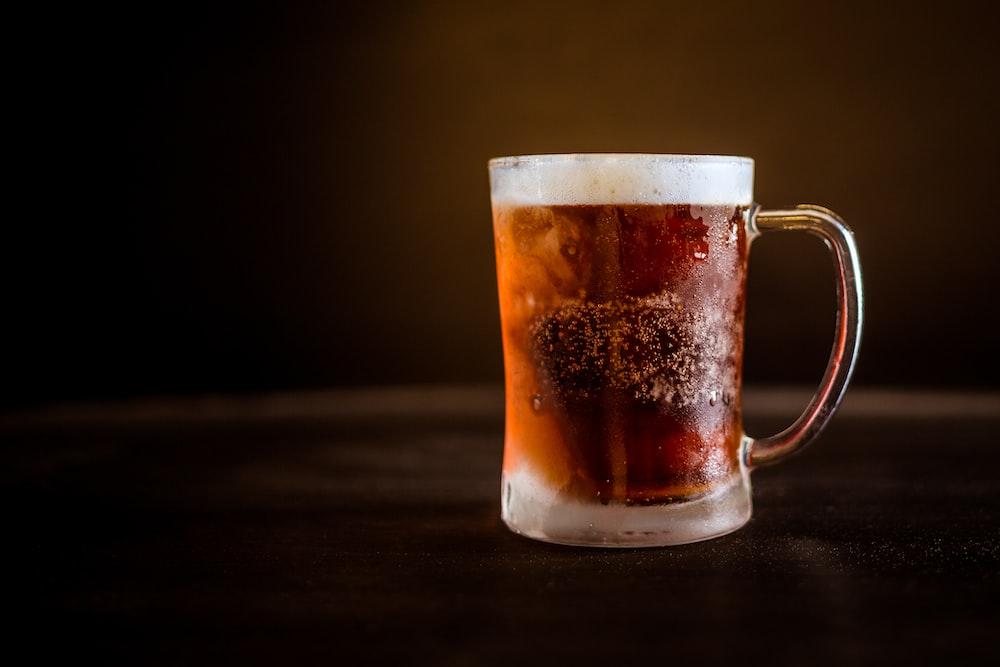 brown liquid on clear glass mug