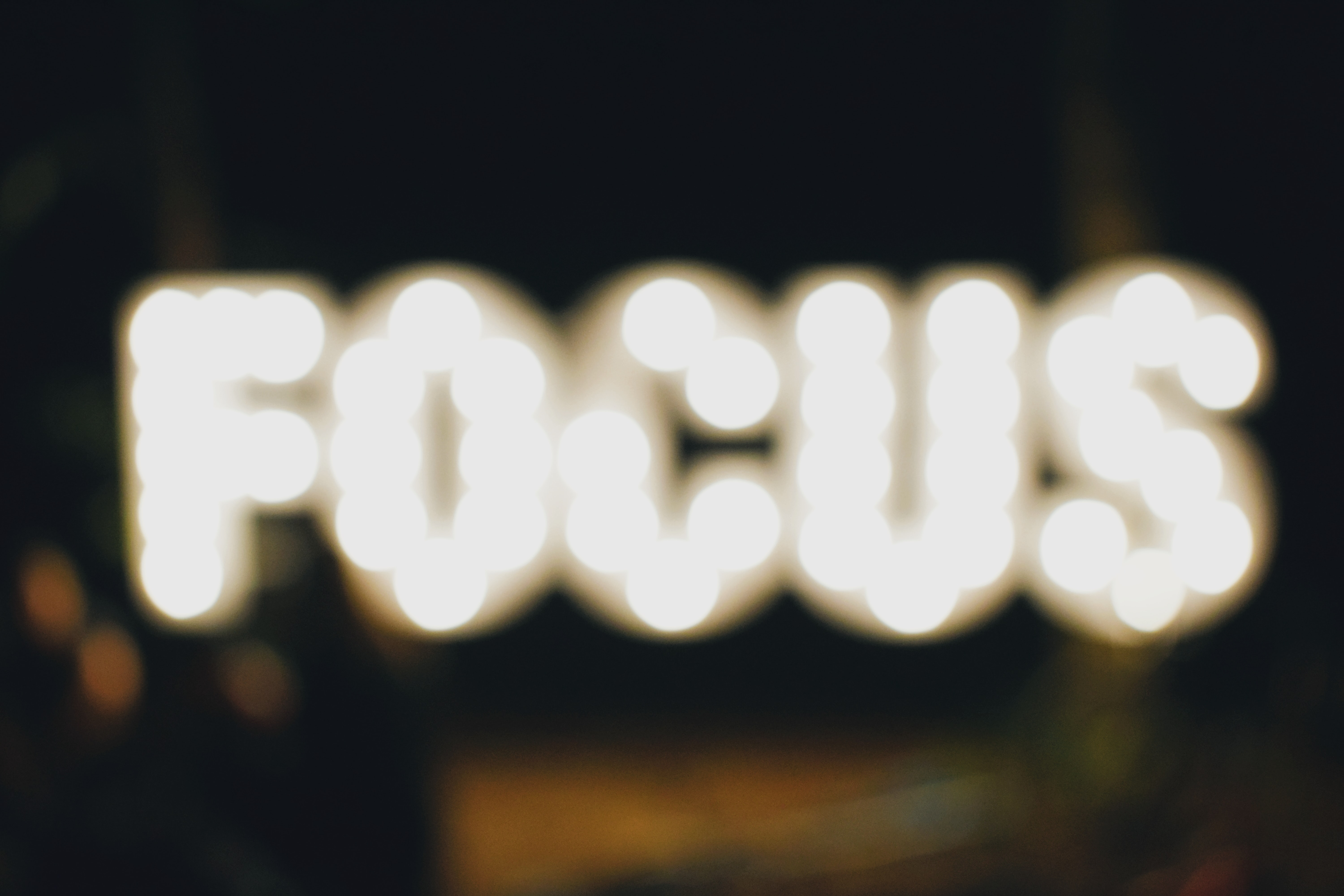 """A blurred image of lights that say """"FOCUS."""""""
