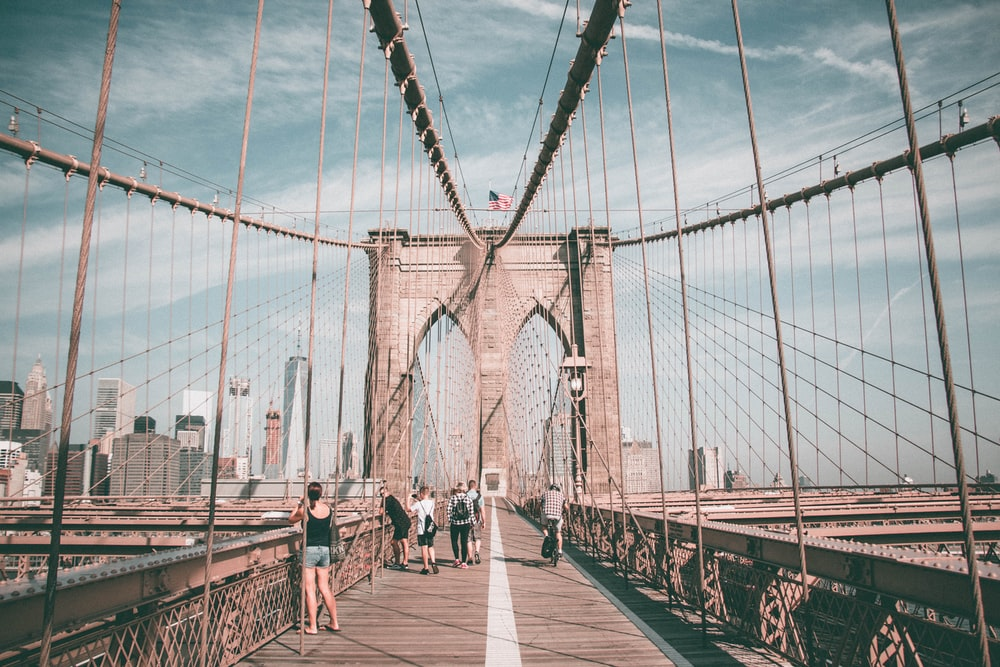 people walking on Brooklyn Bridge during daytime