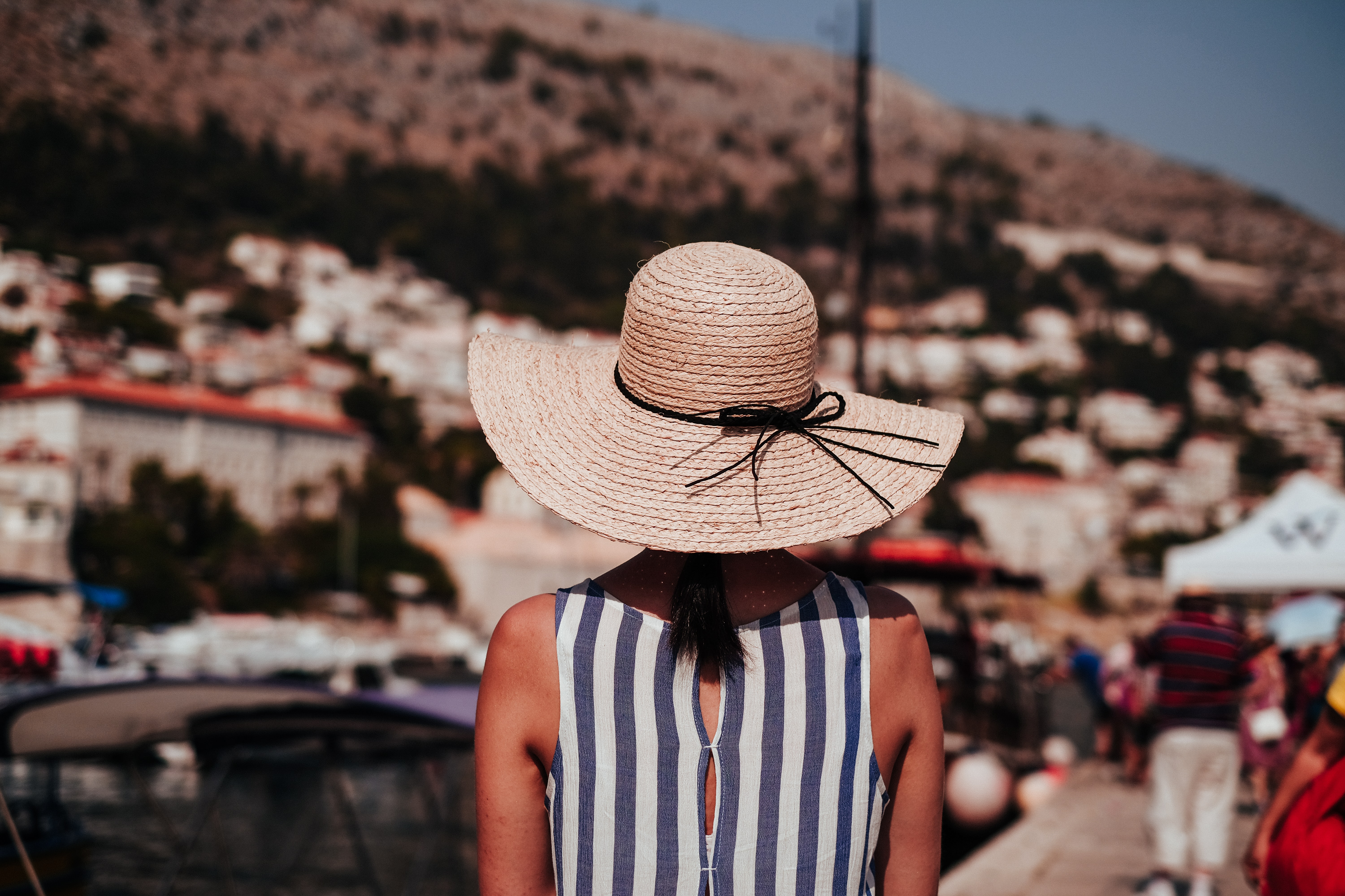 woman wearing gray and white striped sleeveless top and brown sun hat at daytime