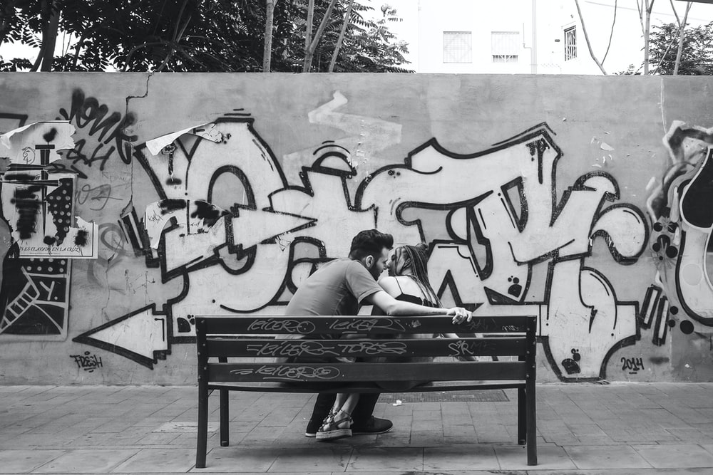 grayscale photo of man and woman sitting on bench
