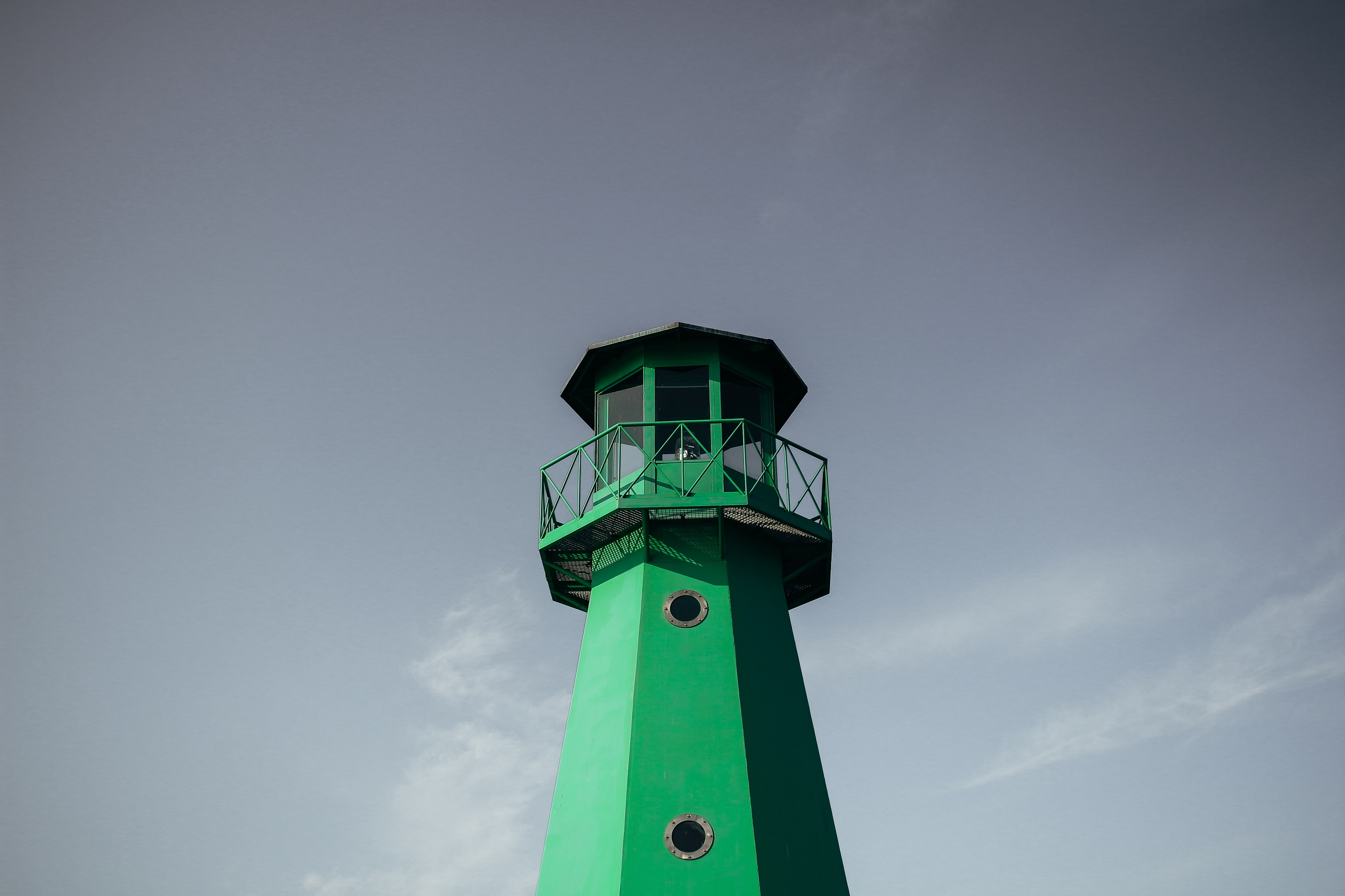 Looking up at a green lighthouse.