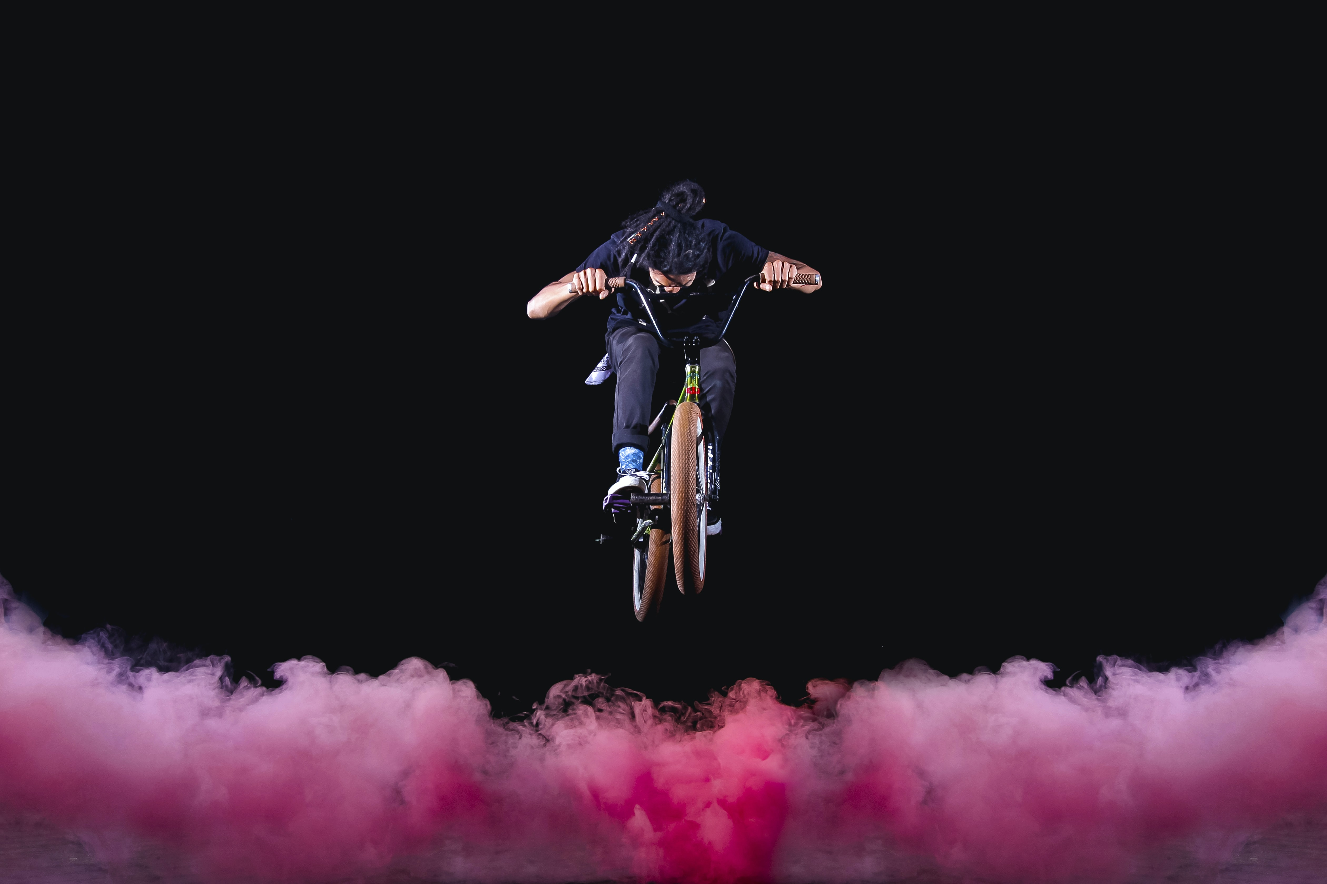 A person jumping their bike over red smoke.