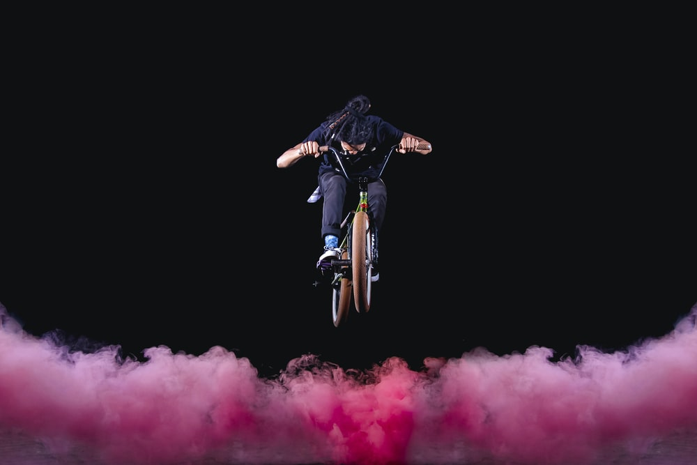man riding BMX bike performing stunts with red fogs