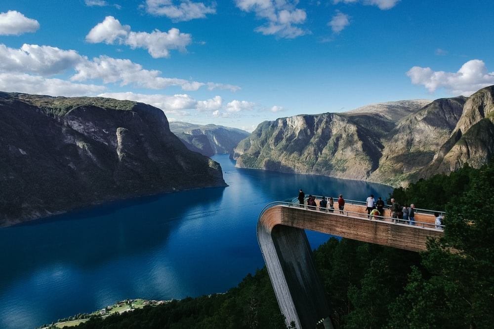 people standing on bridge looking through mountain surrounded by water