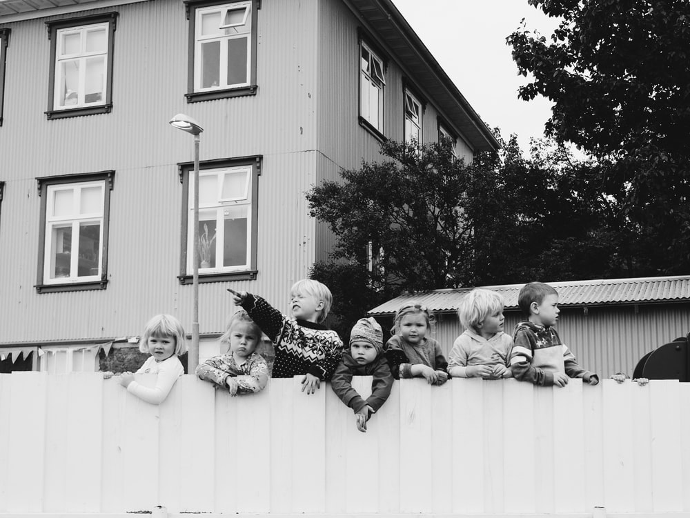 grayscale photo of seven children standing in wooden fence near house