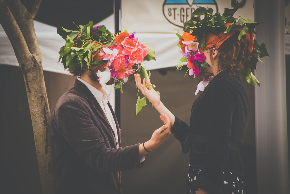 man and woman holding flowers