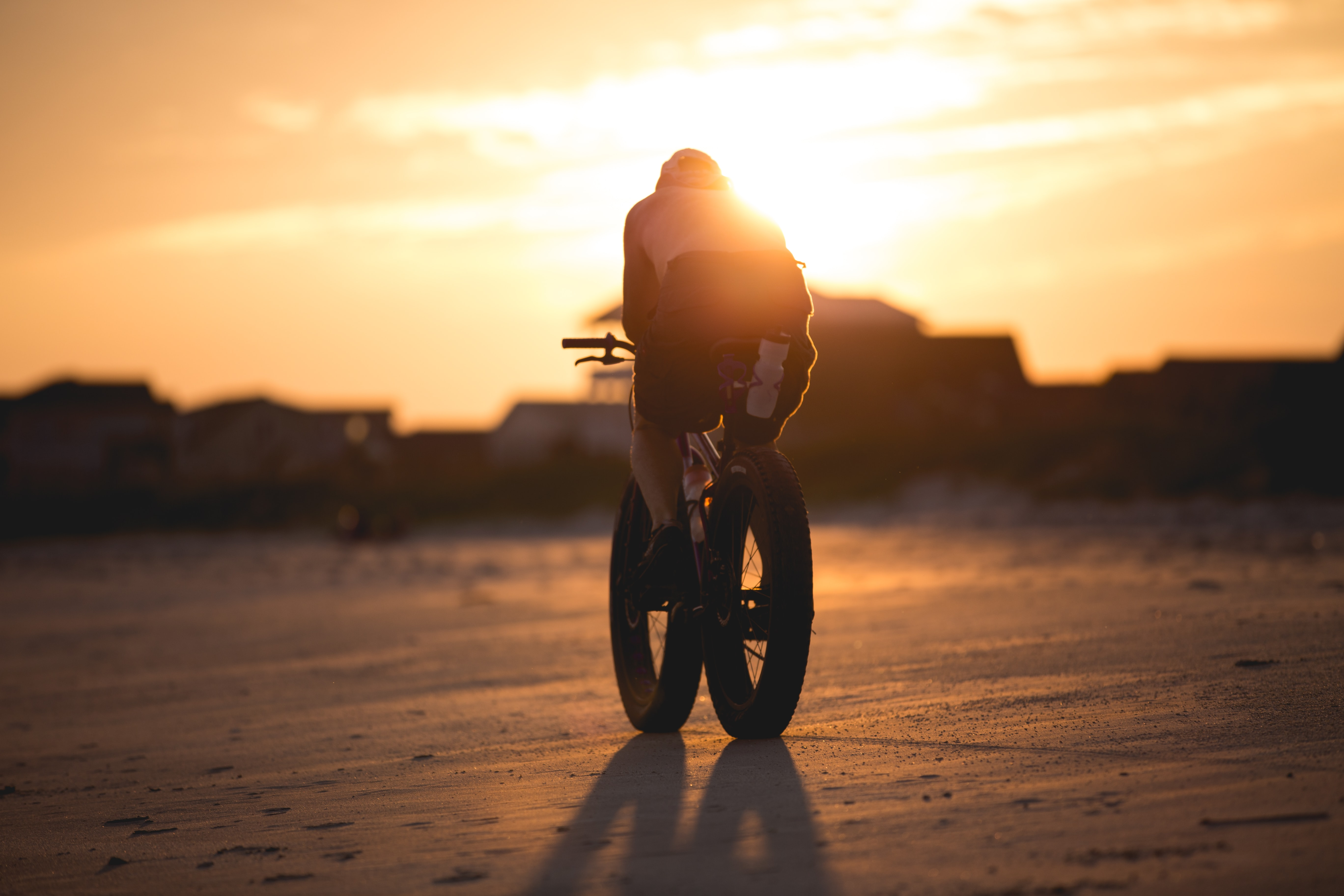 A shirtless man riding a bike with large tires, with the sunset in the background.