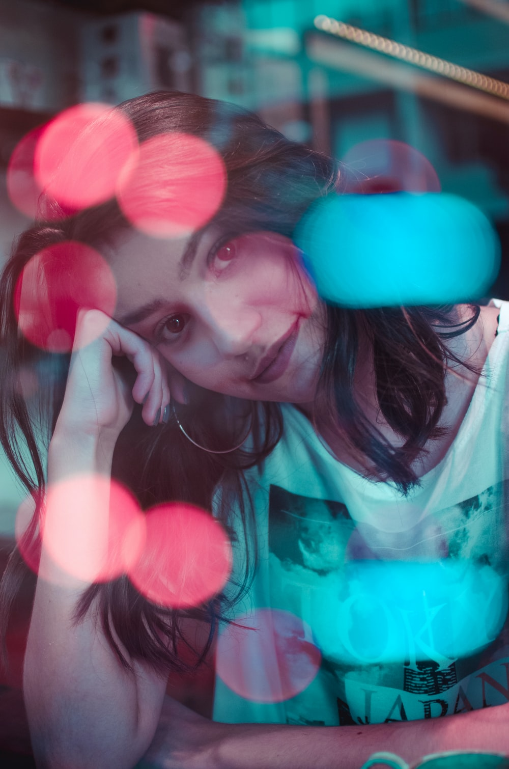 photo of woman wearing white top with bokeh lights