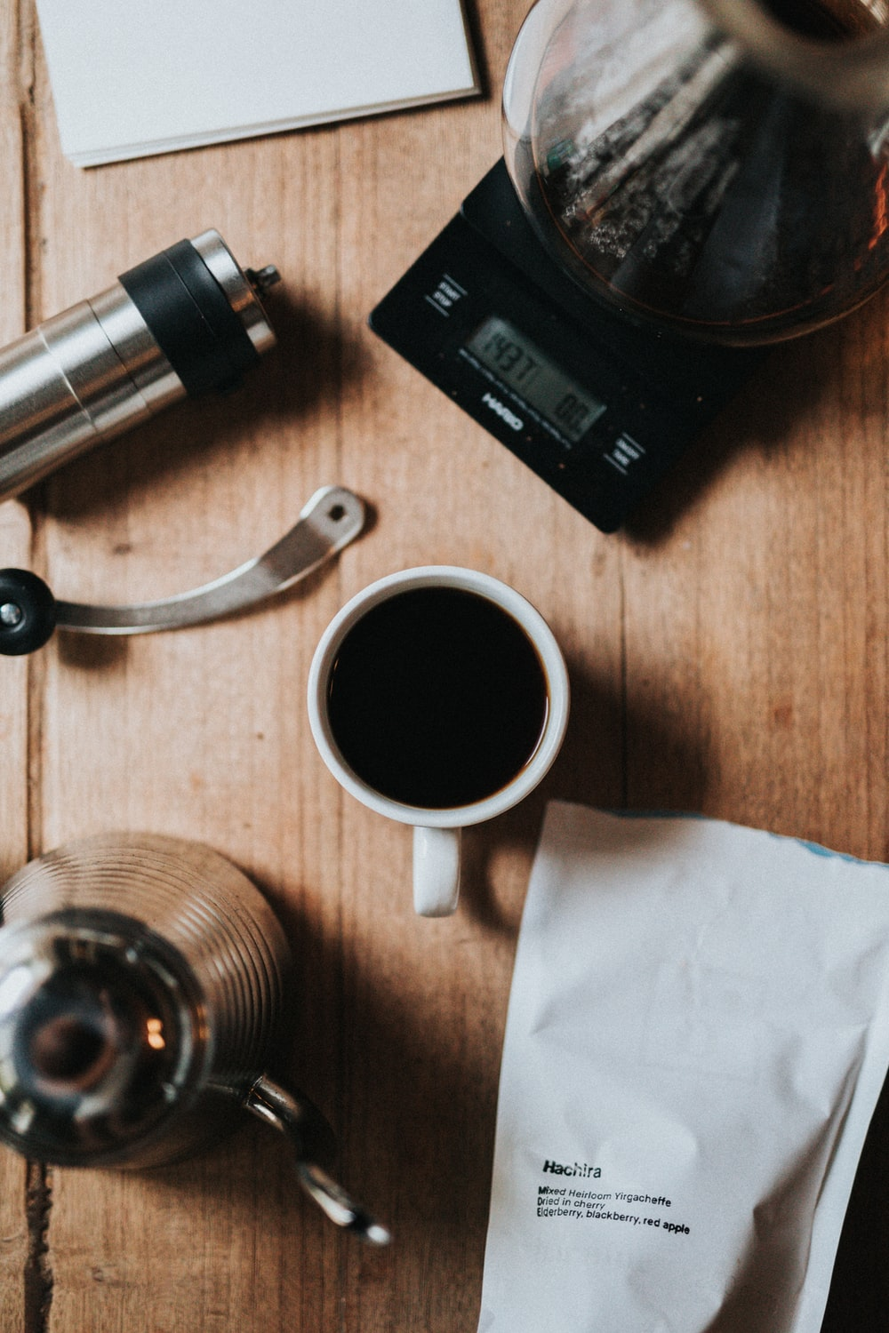 cup of black coffee beside stainless steel teapot