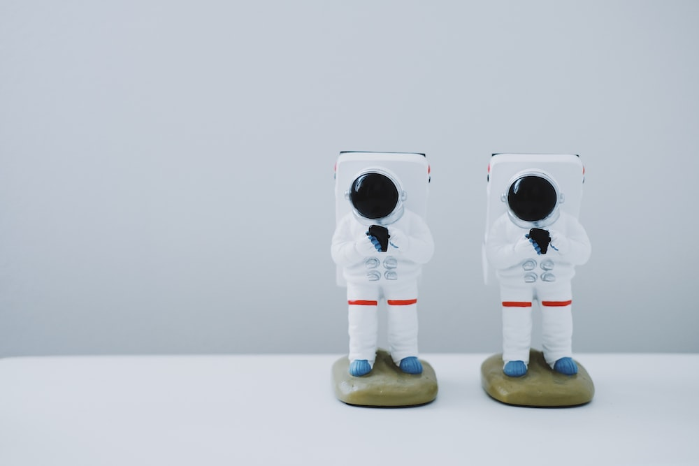 two spacesuit figurines on white surface