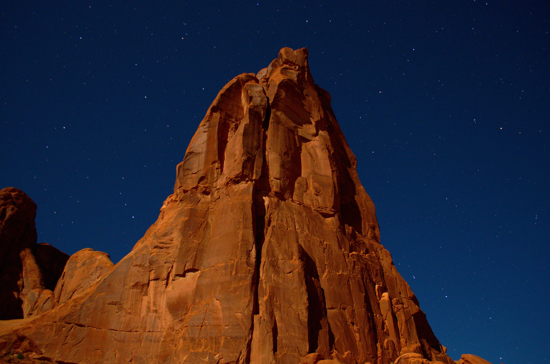 A tall rock formation under a dark blue sky.