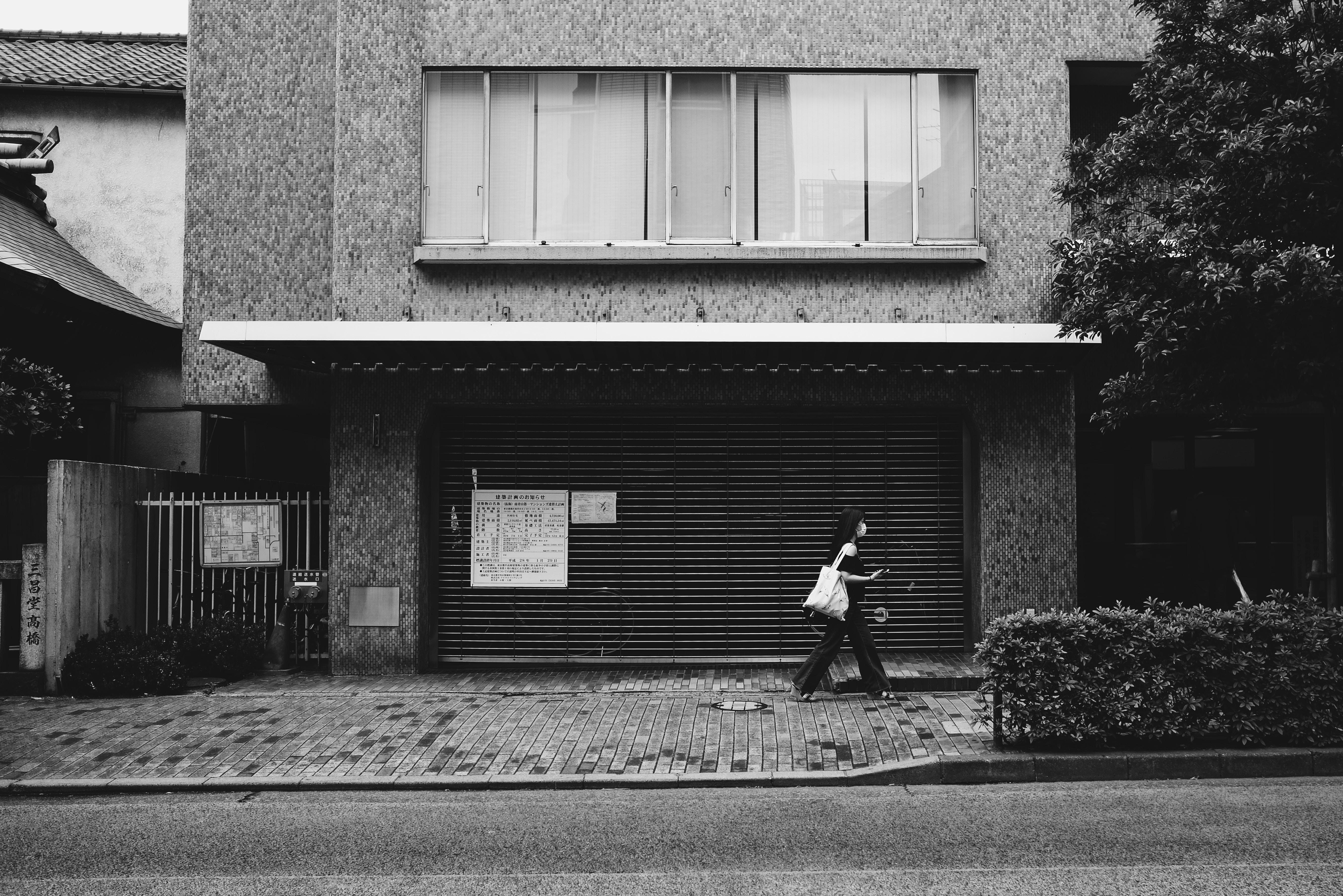 grayscale photo of woman walking beside building