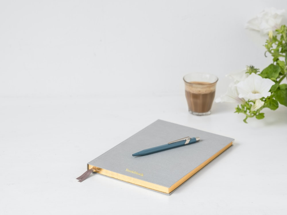 blue click pen on top of gray book near clear drinking glass