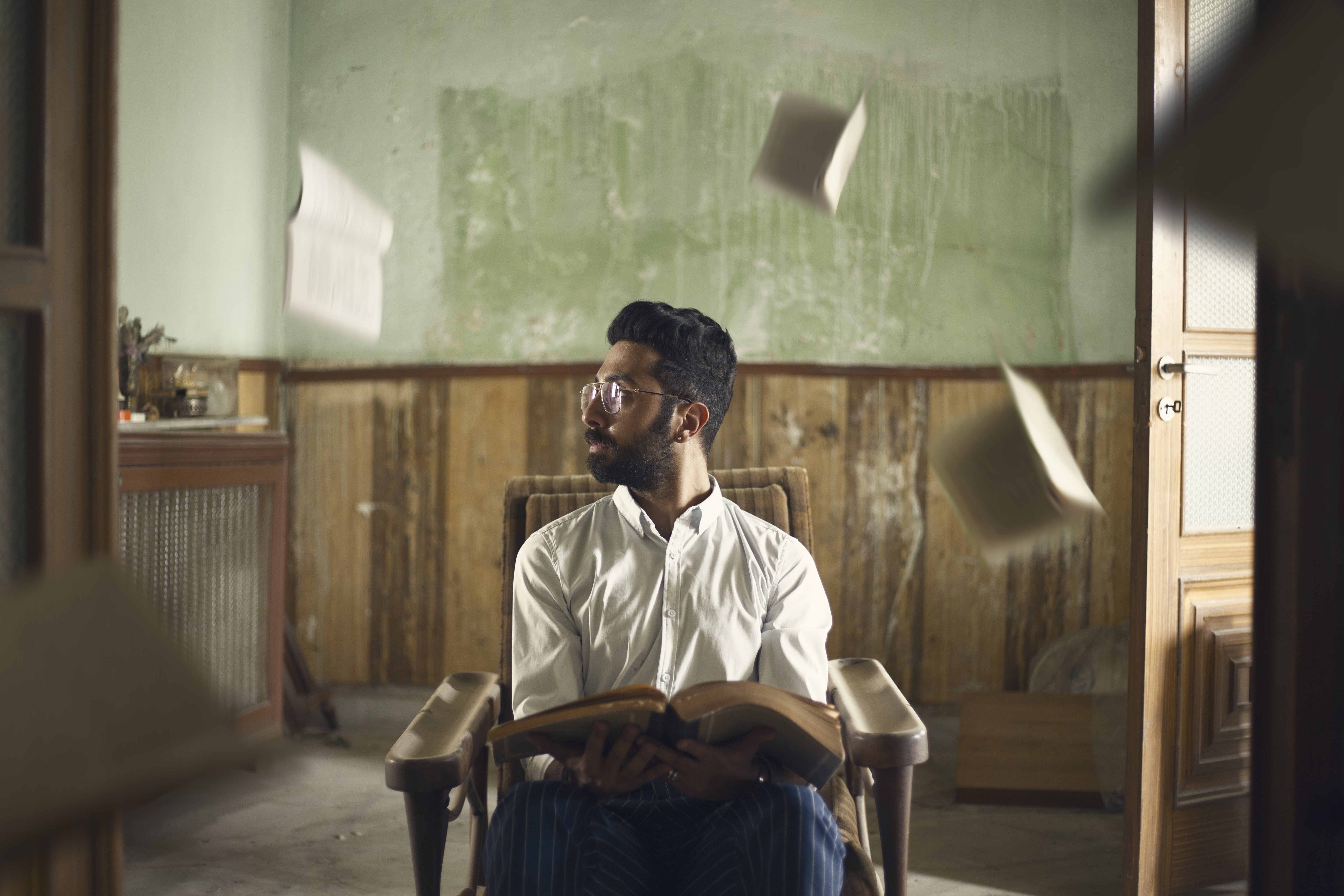 man sitting on brown wooden armchair while carrying brown book