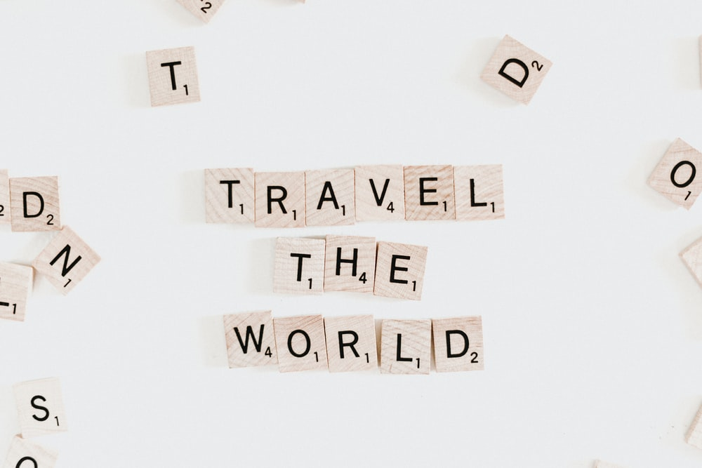 "Scrabble letter pieces that spell ""Travel the world."""