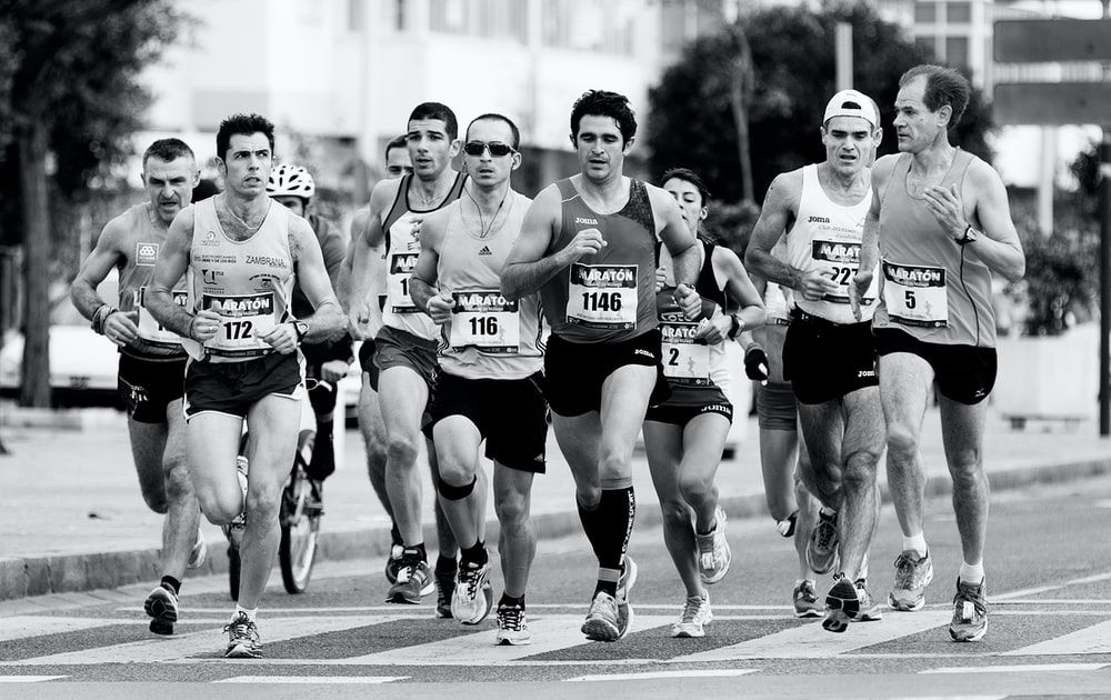 grayscale photo of people performing marathon