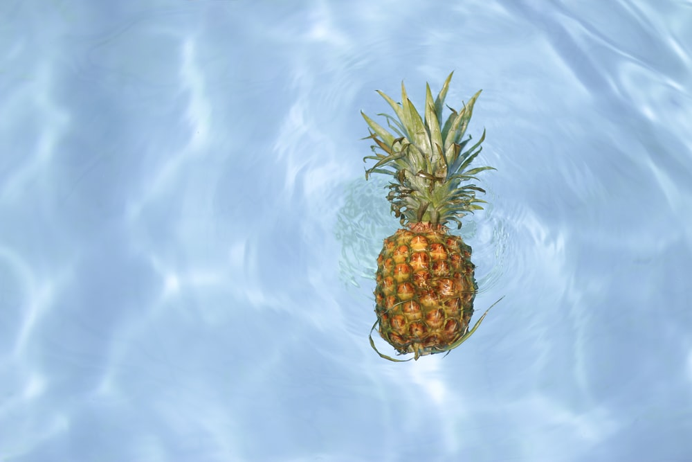 pineapple fruit floating in clear water
