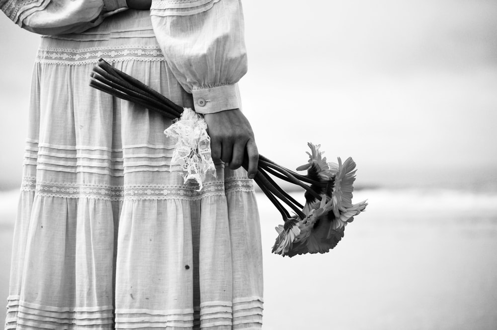person in dress holding bouquet of petaled flowers
