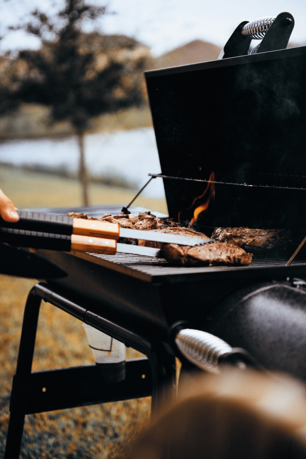 person grilling meat outdoors