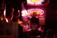 tilt shift photography of red and blue Genesee neon signage