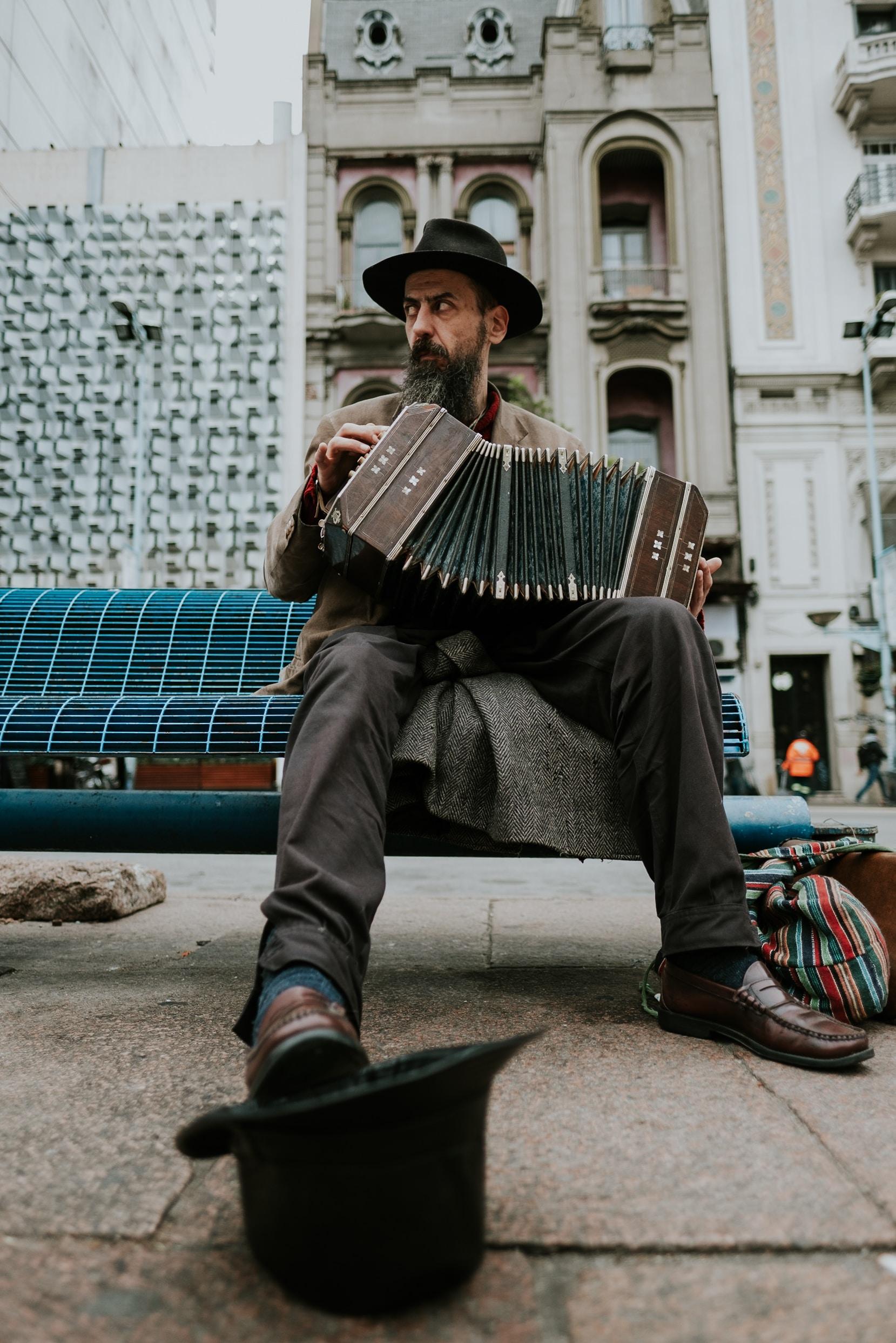 man sitting on bench playing accordion