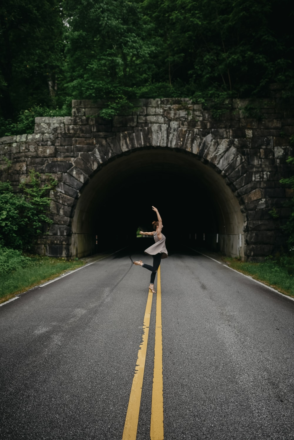 woman in ballet position nearby tunnel