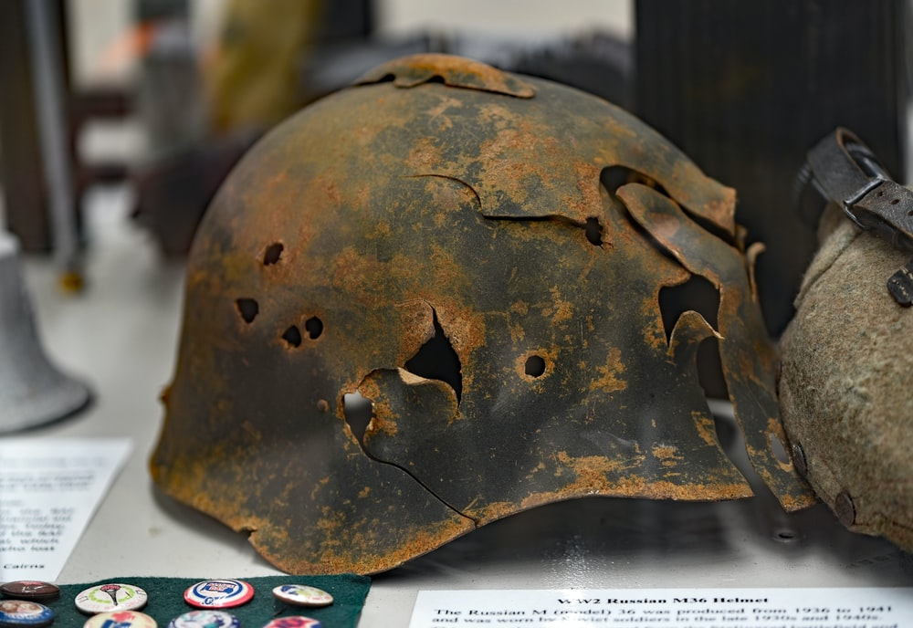 rusty soldier helmet with holes on white surface