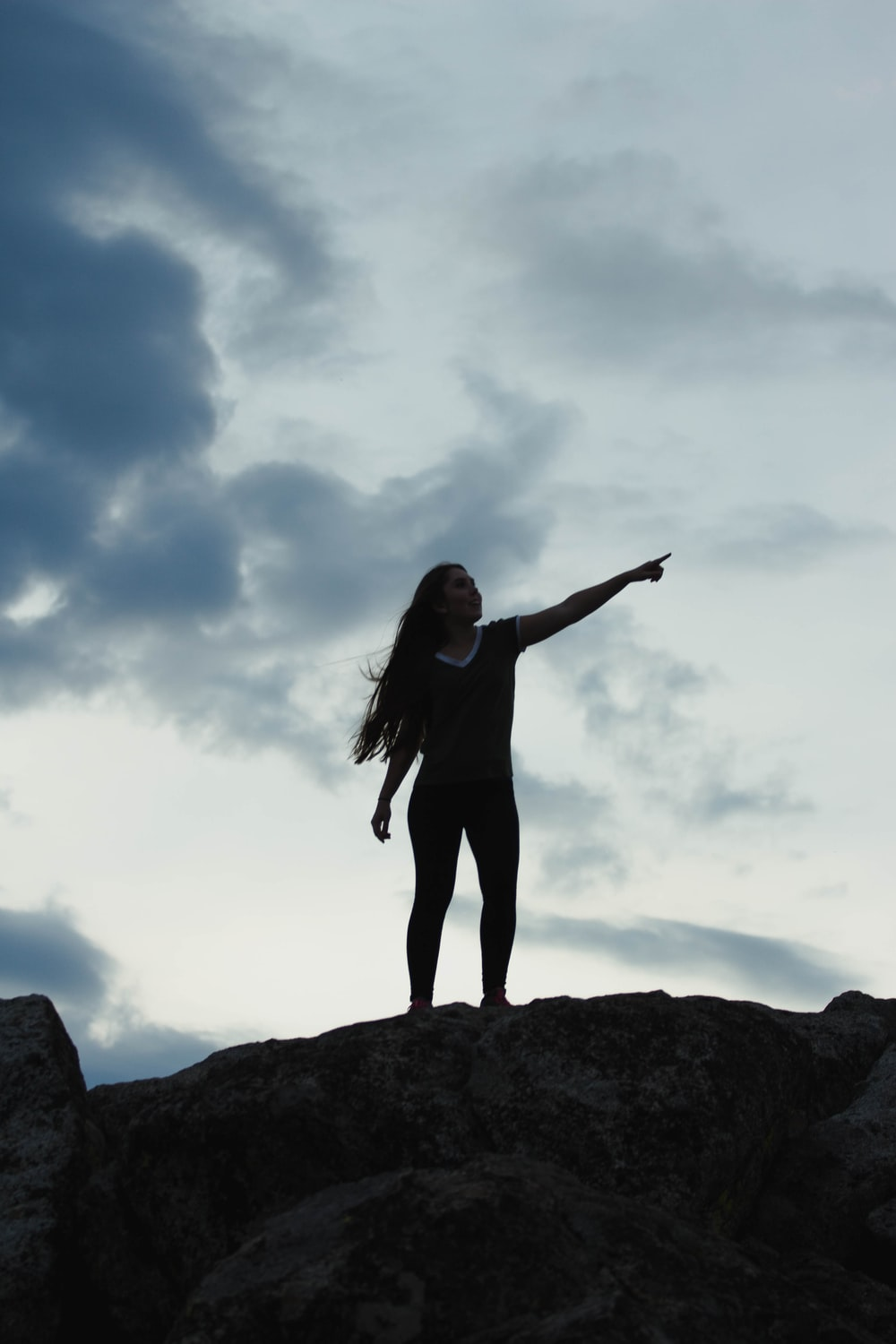 woman in black long sleeve shirt standing on rock under blue sky during daytime