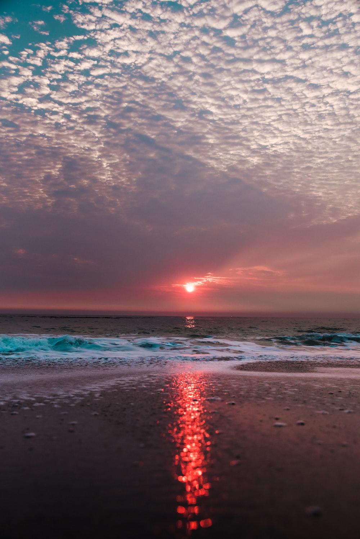 beach under cloudy sky during sunset