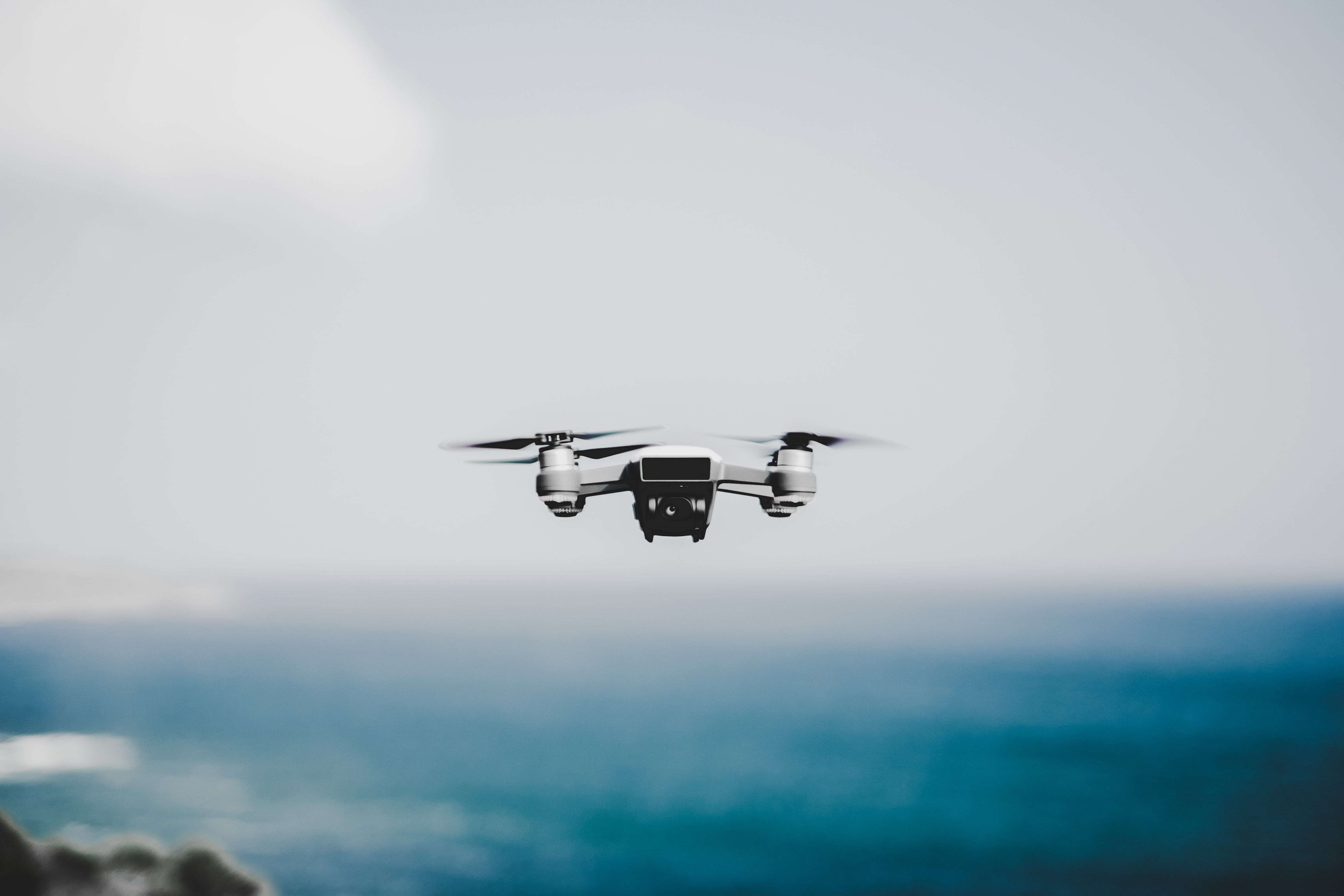 white quadcopter hovering near body of water