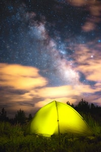 yellow dome tent on green grass field under night sky