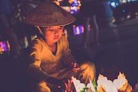 boy wearing brown cap lighting candles during nightime