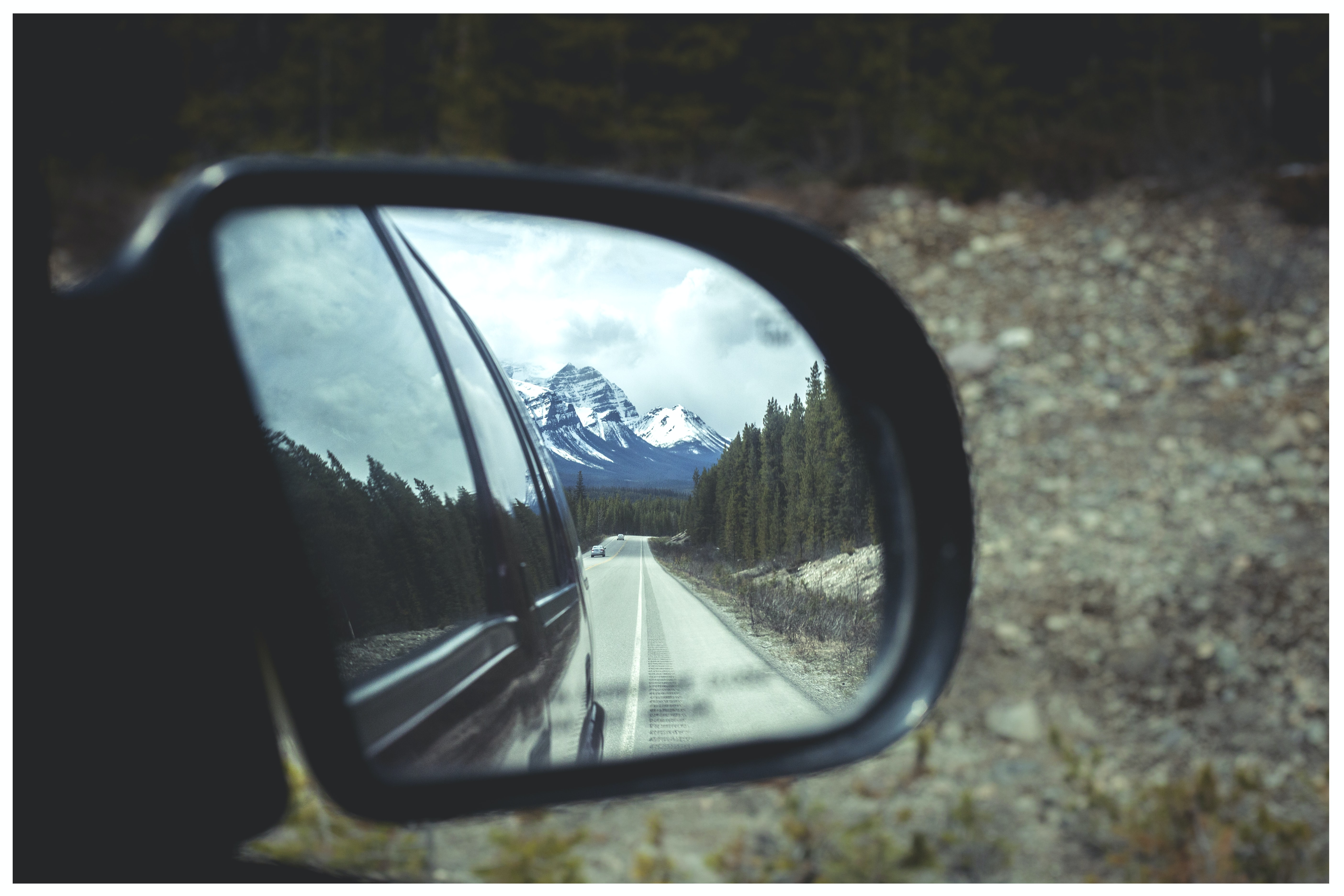 tilt shift photography of side mirror reflecting snow capped mountain