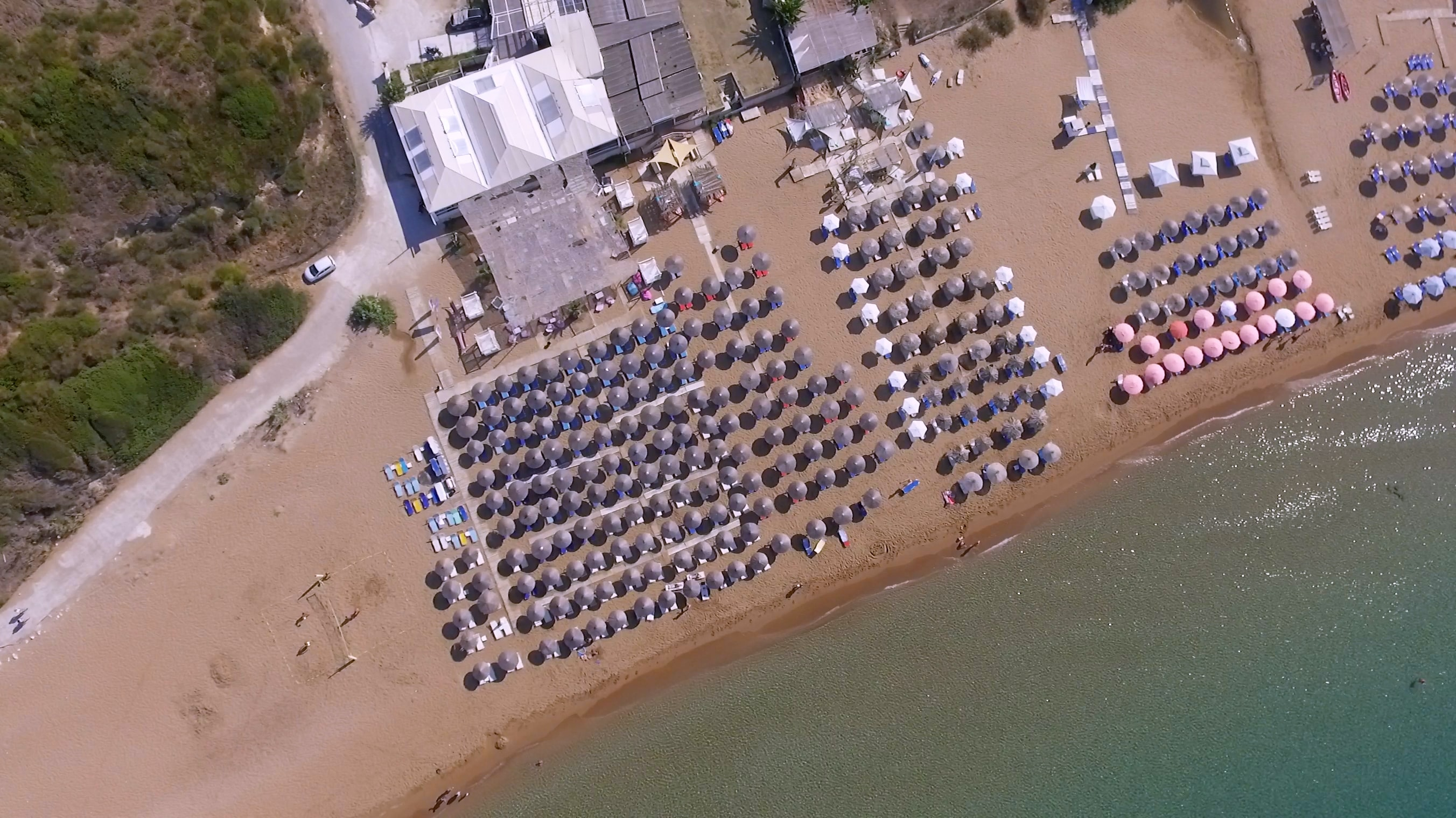 aerial photo of umbrellas near calm body of water at daytime