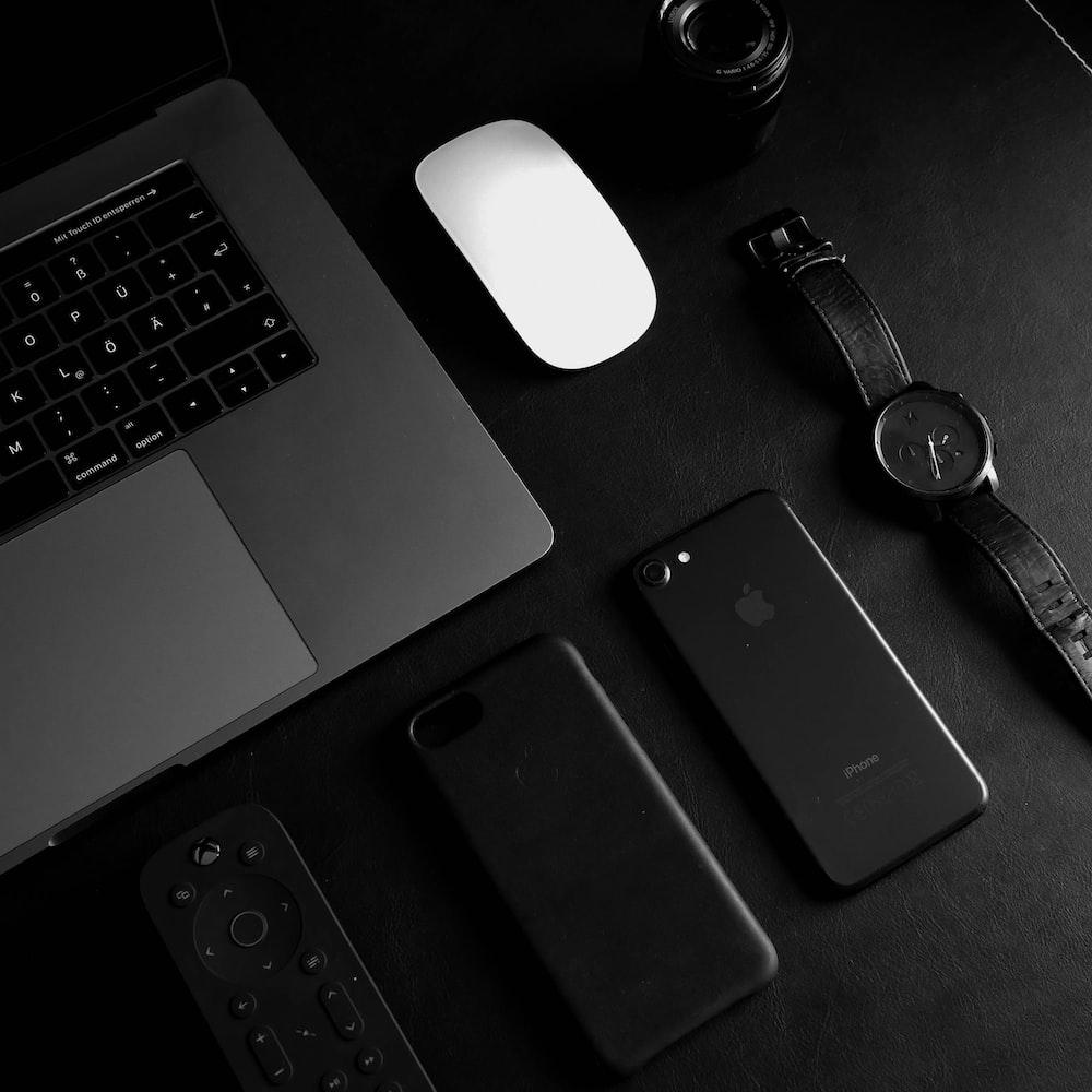jet black iPhone 7 beside analog watch