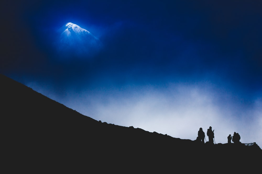 four person standing on cliff silhouette