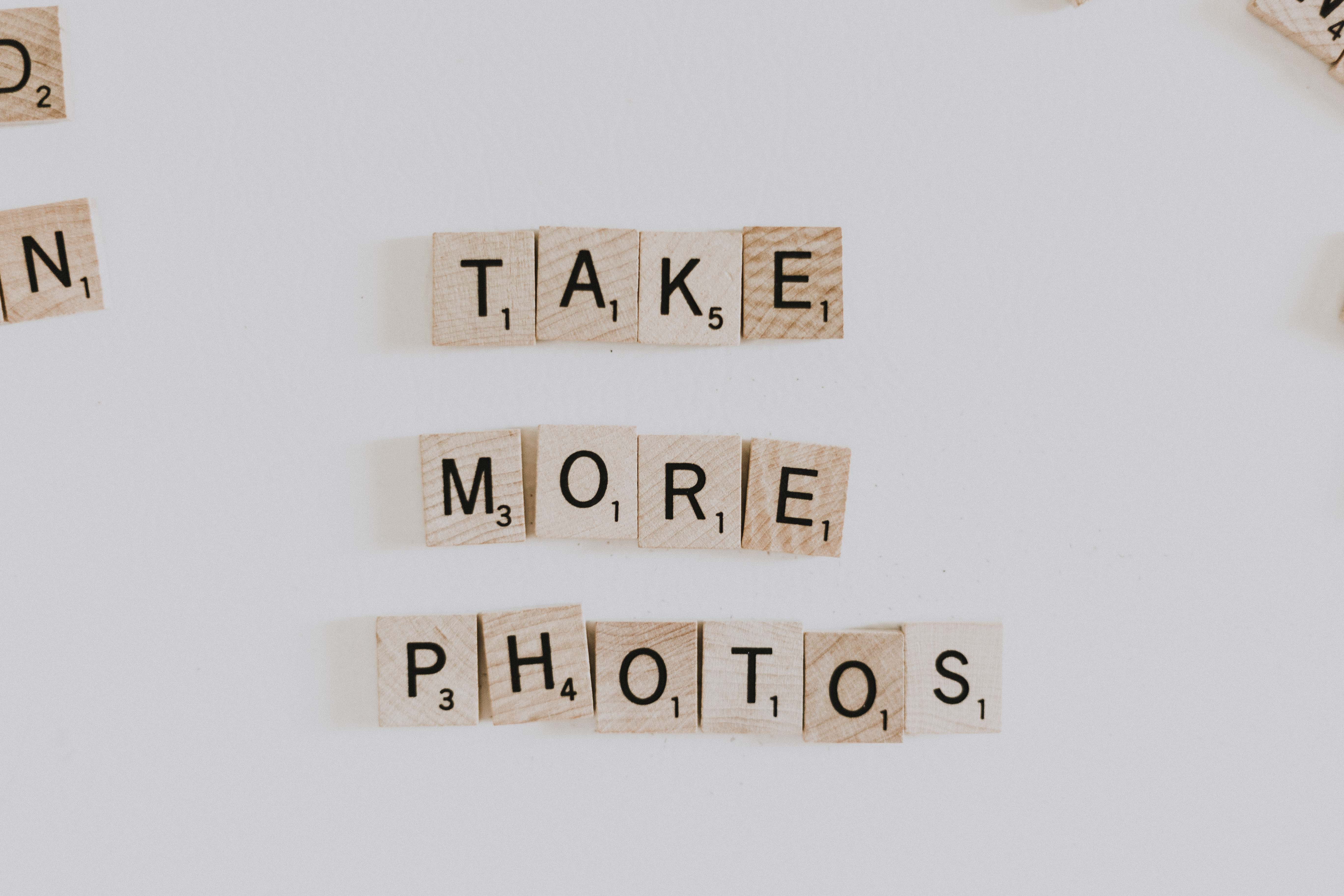 "Scrabble letter pieces that spell out ""Take more photos."""