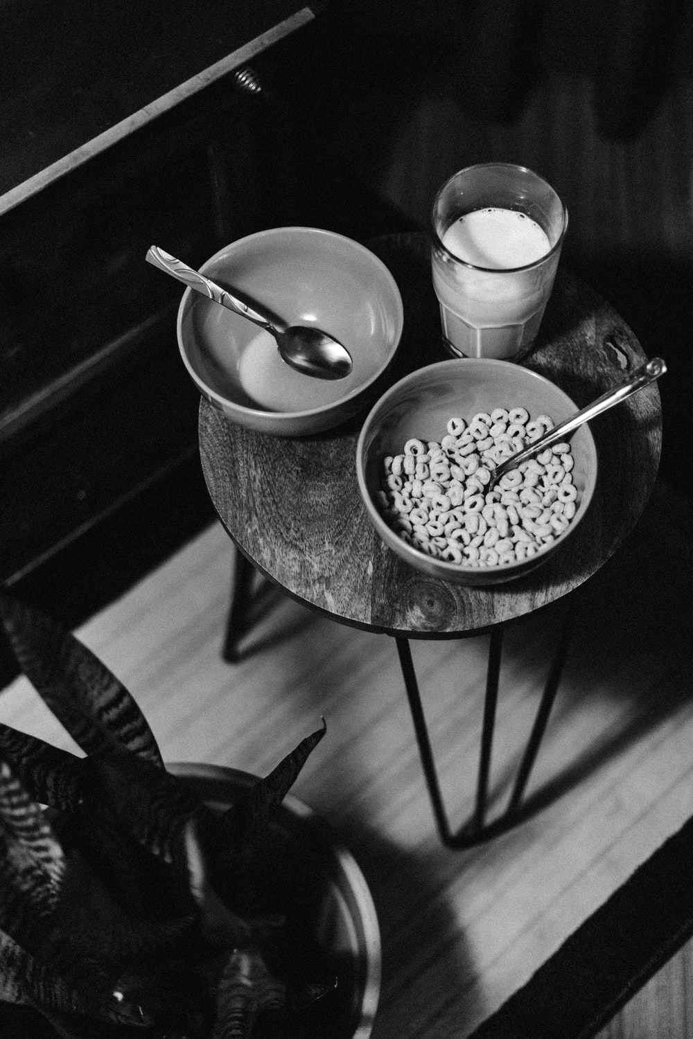 grayscale photo of bowl of cereal beside glass of milk