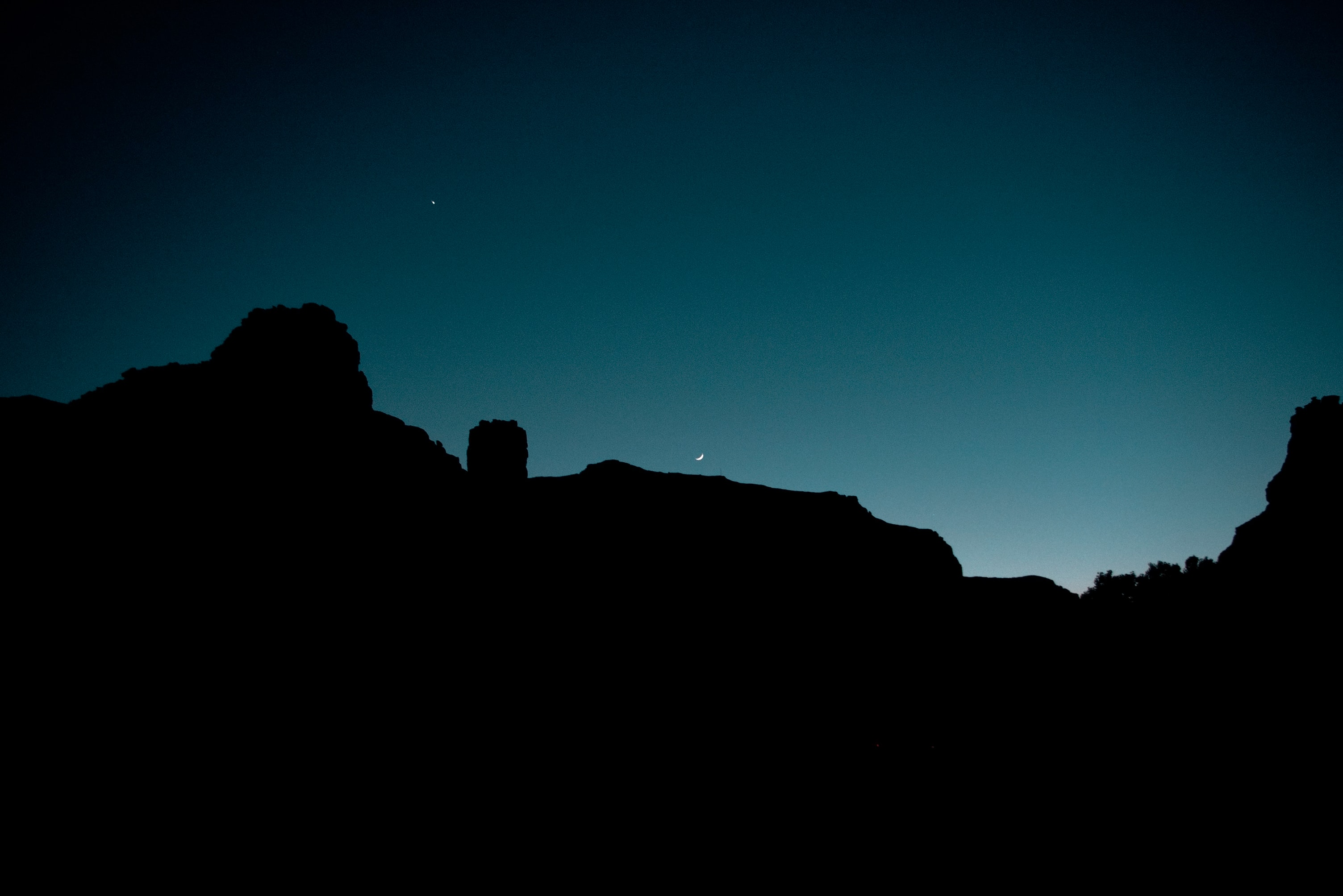 silhouette of mountains under clear sky