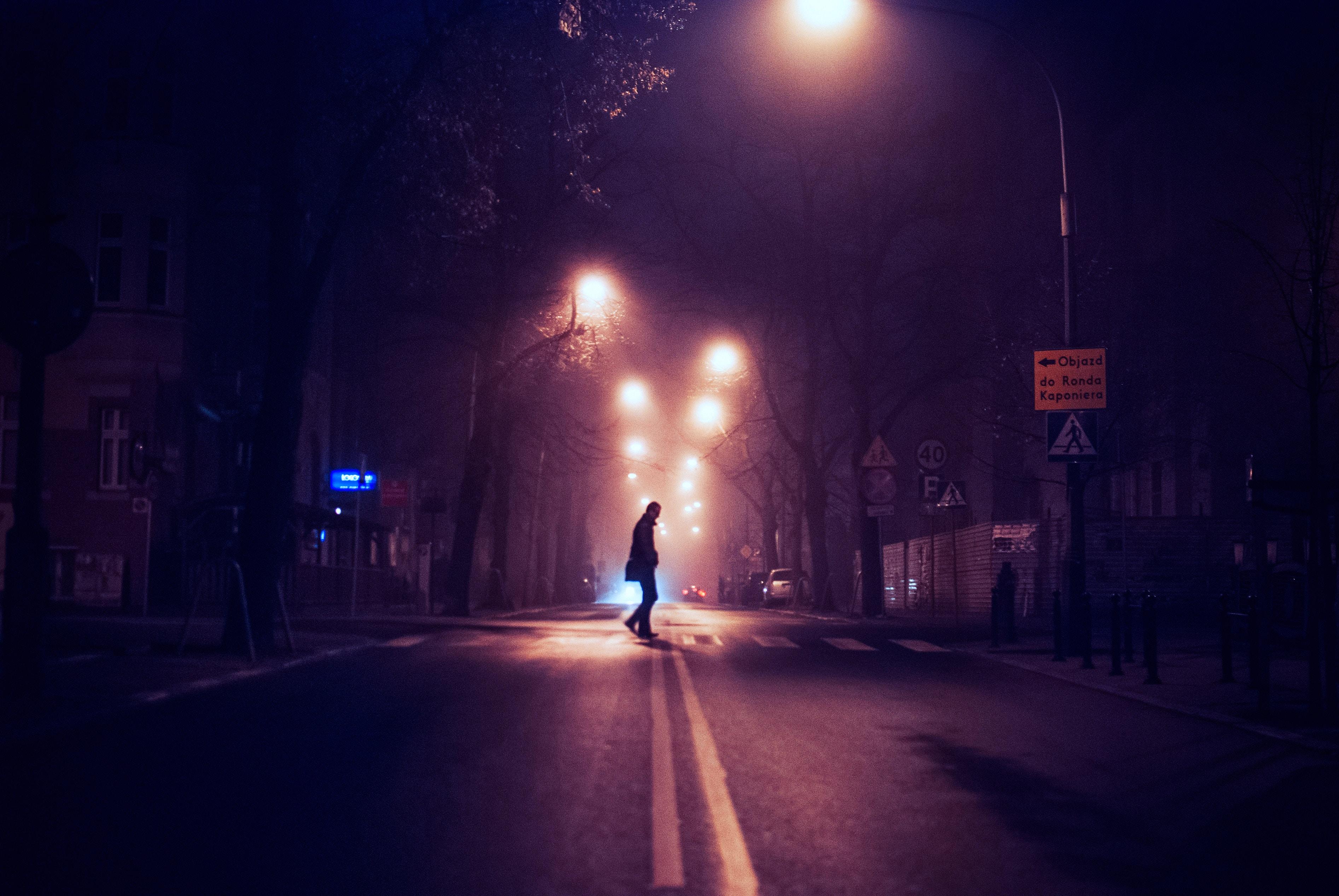 person standing on center asphalt road