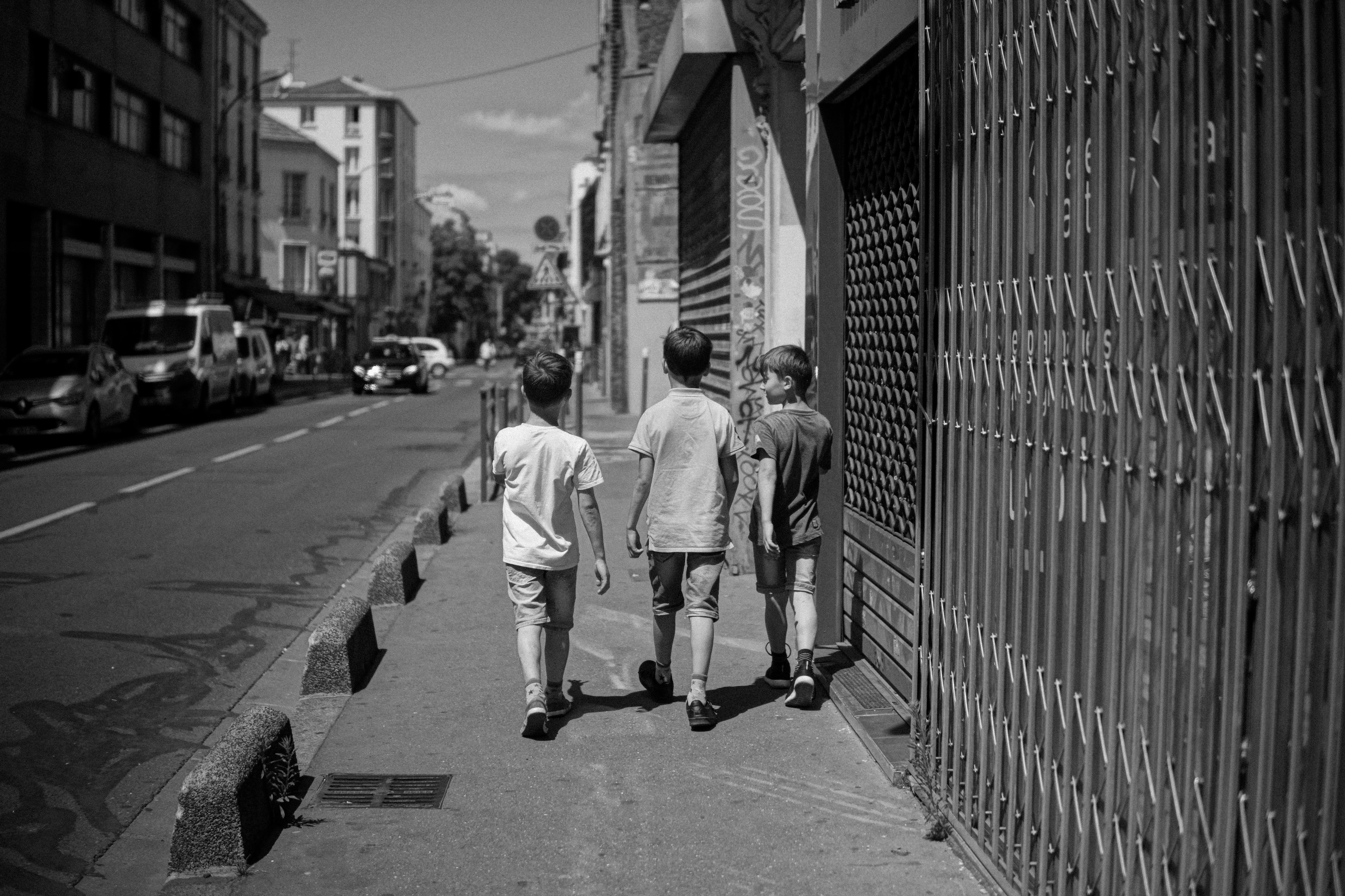 grayscale photography of three children walking at the sidewalk with a car park outside the buildings