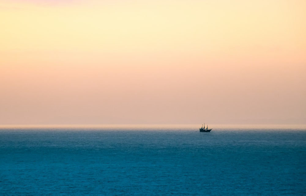 silhouette of boat sailing under cloudy sky during daytime