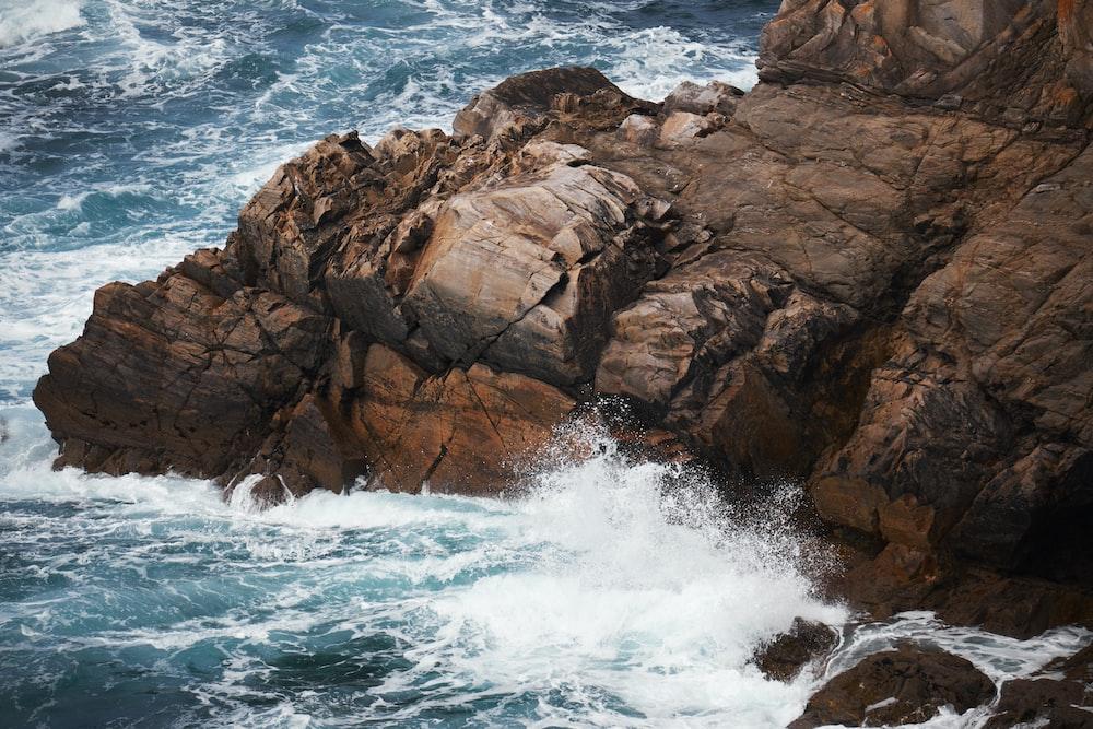 waves crashing on rock at cliff during daytime