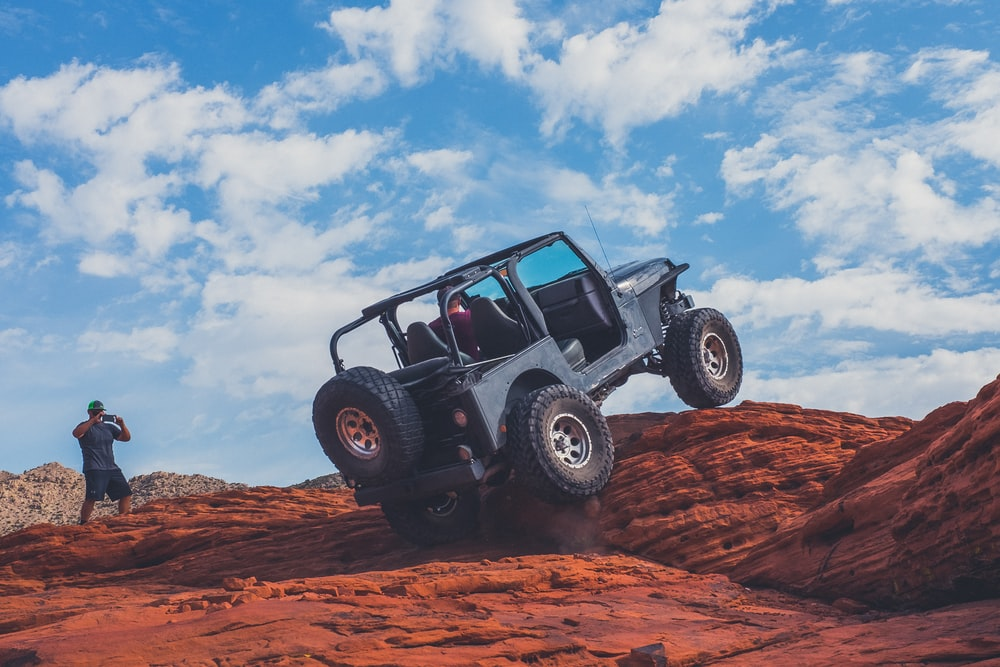 gray 4x4 vehicle climbing the rock during daytime