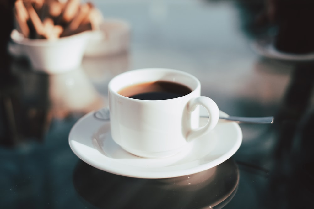 cup of coffee on white ceramic saucer