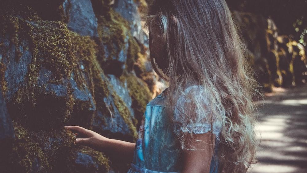 girl wearing lace dress standing near rocks