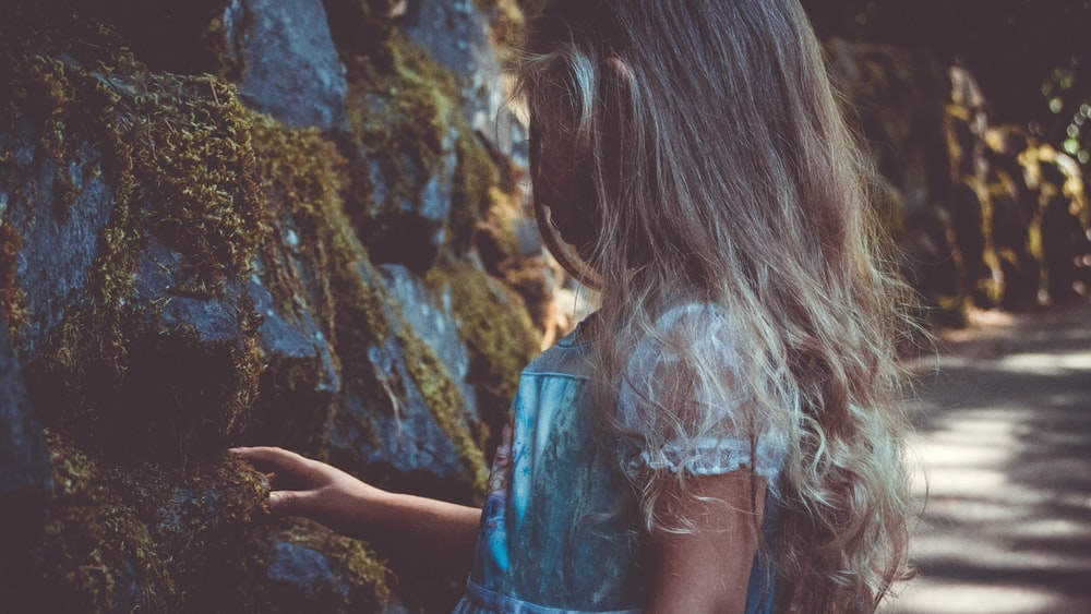 girl wearing lace dress standing near rocks