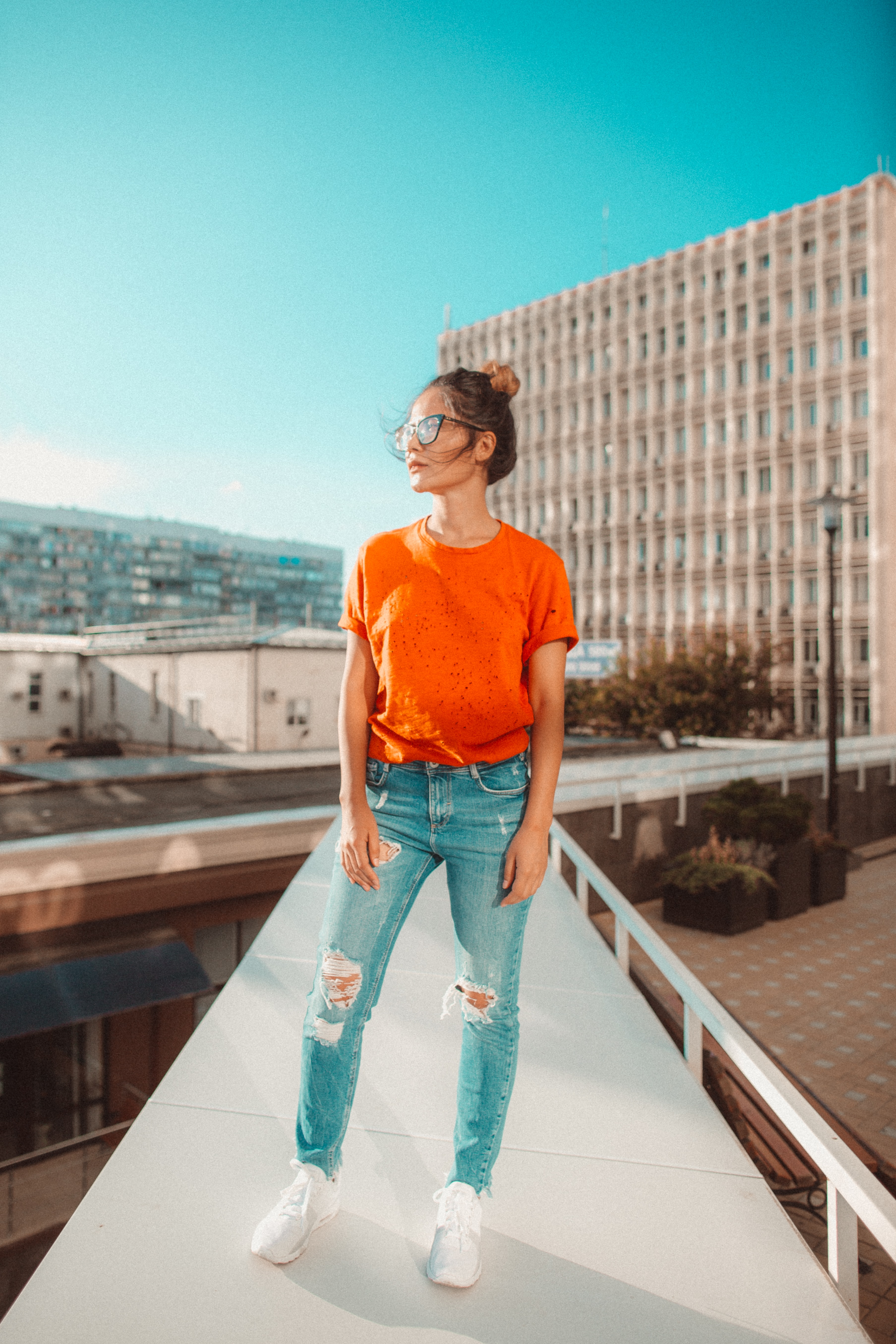 woman in orange crew-neck top standing footbridge