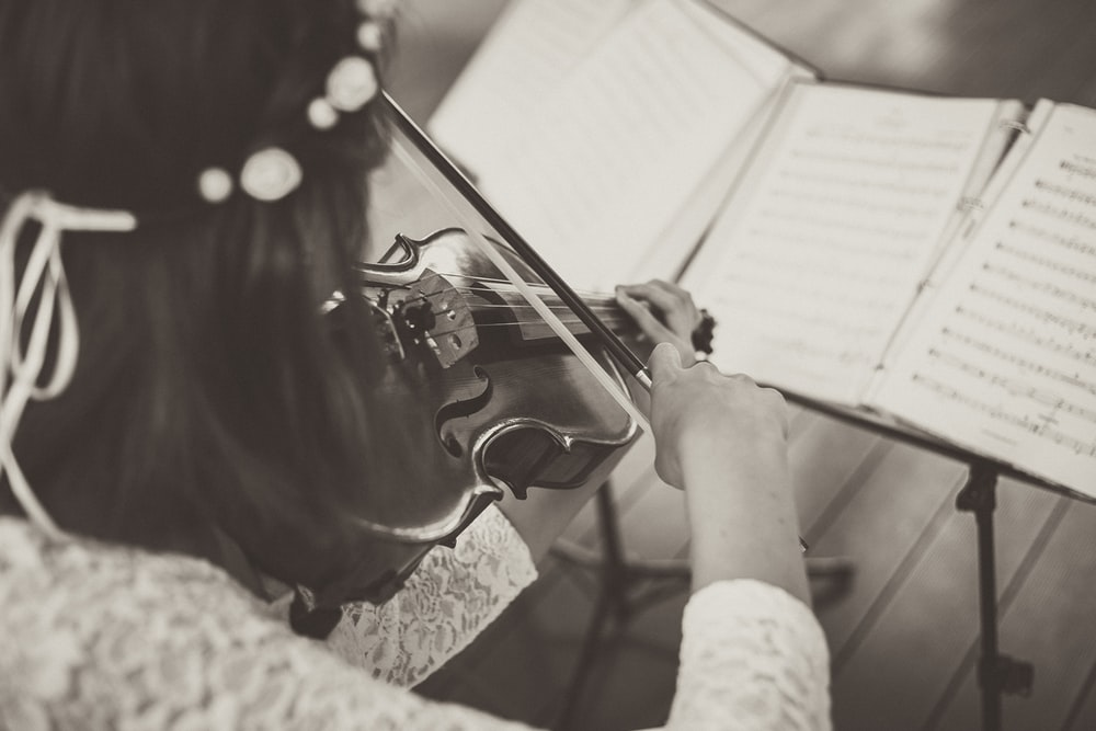 woman wearing lace top playing violin